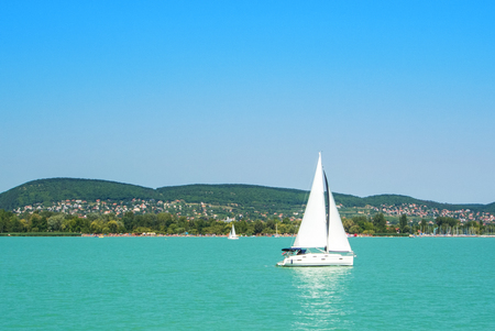 Foto de A view from a ship to bright Balaton lake water and a white yacht with a town, forest and mountains at the background on sunny summer day, Hungary. - Imagen libre de derechos