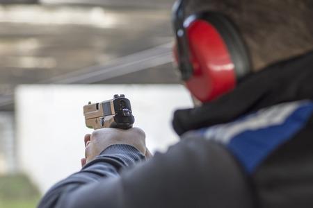 Foto de Shooting with Gun at Target in Shooting Range. Man Practicing Fire Pistol Shooting. - Imagen libre de derechos