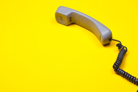 Photo pour Top view of gray telephone handset. receiver and cord on yellow background. - image libre de droit