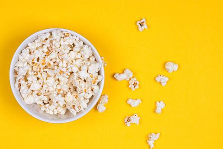 Foto de Bowl of Delicious Popcorn spilling onto a yellow background - Imagen libre de derechos