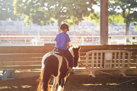 Foto de Portrait of little boy riding a horse. First lessons of horseback riding. Sunny day - Imagen libre de derechos