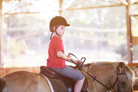 Foto de Portrait of little boy riding a horse. First lessons of horseback riding - Imagen libre de derechos