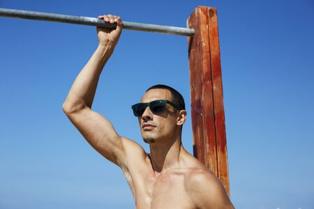 Photo for young muscular man resting and posing on the beach. Wearing sunglasses. - Royalty Free Image