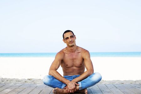Photo for young muscular man in denim pants resting and posing on the beach. - Royalty Free Image