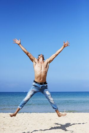Photo for young muscular man resting and posing on the beach. Jump in the air. - Royalty Free Image