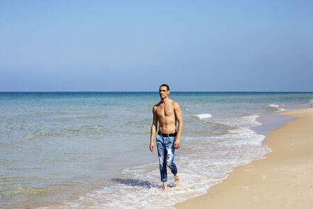 Photo for young muscular man resting and posing on the beach. A young man walks by the sea. - Royalty Free Image