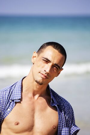 Photo for young muscular man resting and posing on the beach. - Royalty Free Image
