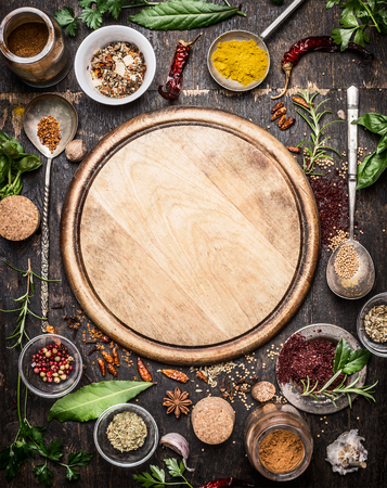 variety of herbs and spices  around empty cutting board on rustic wooden background, top view.Creative and national cuisine  and cooking concept.