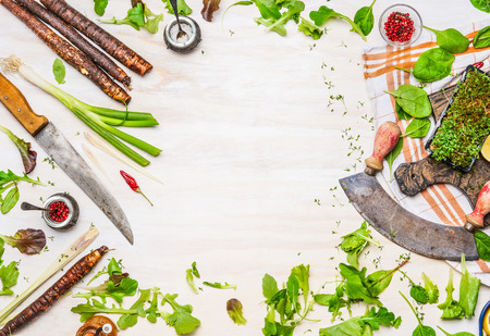 Delicious fresh vegetables, spices and seasoning for tasty cooking with kitchen knife on white wooden background, top view, frame. Healthy  clean or vegetarian food concept.