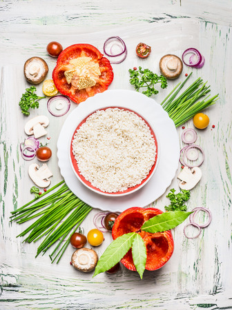 Risotto rice dish  and various vegetables and seasoning ingredients  for tasty vegetarian cooking on light  rustic wooden background, top view composing. Healthy eating and diet food concept.