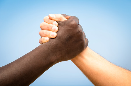 Photo for Black and white human hands in a modern handshake to show each other friendship and respect - Arm wrestling against racism - Royalty Free Image