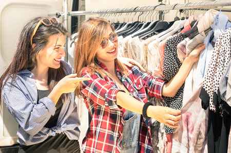 Photo pour Young beautiful women at the weekly cloth market - Best friends sharing free time having fun and shopping in the old town in a sunny day - image libre de droit