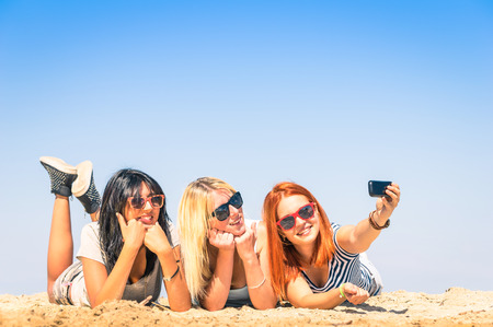 Foto de Group of girlfriends taking a selfie at the beach - Concept of friendship and fun in the summer with new trends and technology - Best friends enjoying the moment with modern smartphone - Imagen libre de derechos