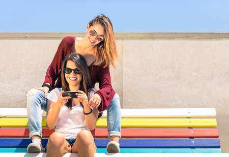Foto de Best friends enjoying time together outdoors with smartphone - Concept of new technology with two girlfriends having fun on a multicolored bench - Imagen libre de derechos