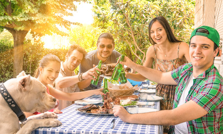 Photo for Group of happy friends eating and toasting at garden barbecue - Concept of happiness with young people at home enjoying food together - Royalty Free Image