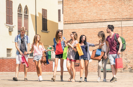 Photo pour Group of happy best friends with shopping bags in the city center - Tourists walking and having fun in the summer around the old town - University students during a break in a sunny day - image libre de droit