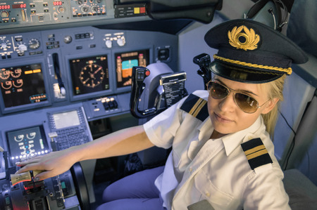 Photo pour Beautiful blonde woman pilot wearing uniform and hat with golden wings - Modern aircraft cockpit ready for take off - Concept of female emancipation - image libre de droit