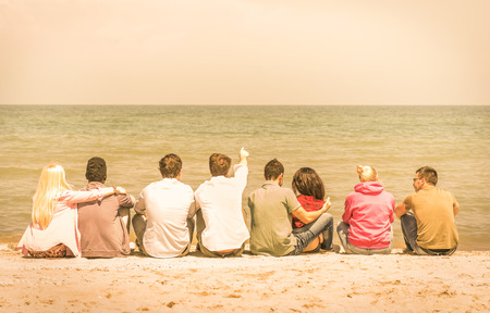 Photo for Group of international multiracial friends sitting at the beach talking with each other and contemplating the sea - Concept of multi cultural friendship against racism - Warm vintage filtered look - Royalty Free Image