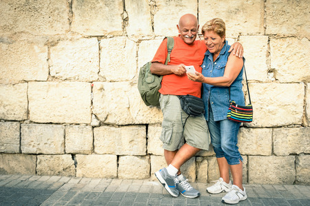Foto de Happy senior couple having fun with a modern smartphone - Concept of active elderly and interaction with new technologies - Travel lifestyle without age limitation - Imagen libre de derechos