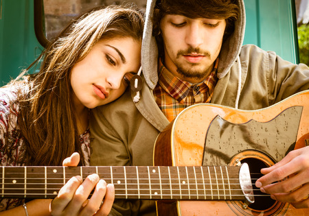 Photo pour Romantic young Couple playing Guitar outdoor after the Rain - image libre de droit
