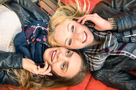 Foto de Best friends enjoying time together outdoors with smartphone - Concept of new technology with two girlfriends having fun on a vintage wood bench and red pillows - Imagen libre de derechos