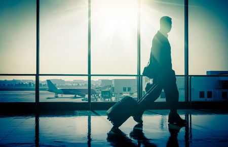 Photo pour Business man at international airport with suitcase - image libre de droit