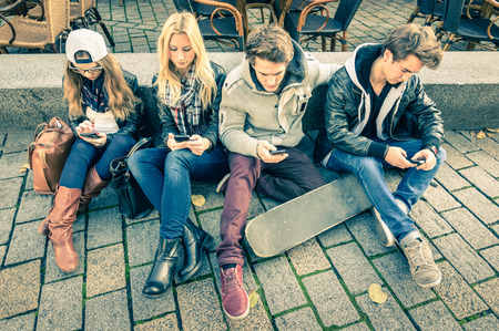 Foto de Group of young hipster friends playing with smartphone with mutual disinterest towards each other - Modern situation of technology interaction in alienated lifestyle - Internet wifi connection - Imagen libre de derechos