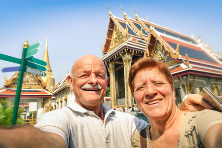 Foto de Senior happy couple taking a selfie at Grand Palace temples in Bangkok - Thailand adventure travel to asian destinations - Concept of active elderly and fun around the world with new technologies - Imagen libre de derechos