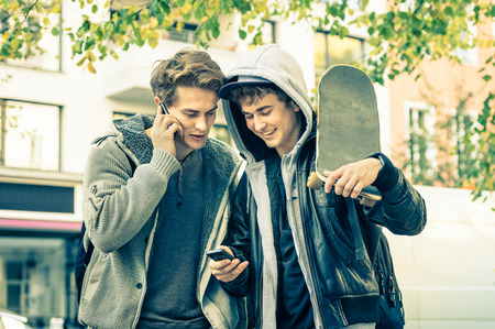 Photo for Young hipster brothers having fun with smartphone - Best friends sharing free time with new trends technology - Guys enjoying everyday life moments texting connected with modern smart phone device - Royalty Free Image