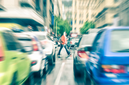 Photo for Person crossing the road during rush hour in Cape Town - Concept of connection between people and traffic jam on a vintage filtered look - Radial zoom defocusing of commuter cars on urban city streets - Royalty Free Image