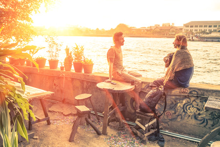 Photo for Couple of best friends travelers talking at sunset - Travel concept around the world with exclusive destinations - Royalty Free Image