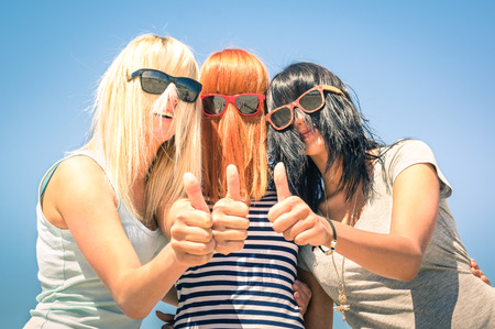 Photo pour Group of young girlfriends with focus on colored funny hair and sunglasses - Concept of friendship and fun in the summer expressing positivity with thumbs up - Best friends sharing happiness together - image libre de droit