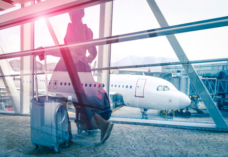 Foto de Travel concept with woman and suitcase moving fast to airport terminal gate - Double exposure look with focus on the aircraft in the background - Violet marsala sun flare with vintage filtered editing - Imagen libre de derechos