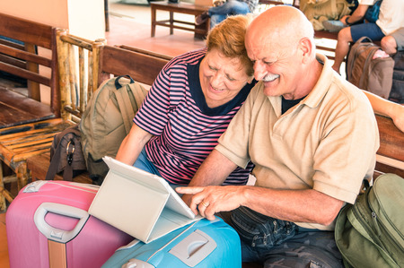 Photo pour Happy senior couple sitting with digital laptop and travel baggage during adventure trip around the world - Concept of active elderly lifestyle and interaction with new trends and technologies - image libre de droit