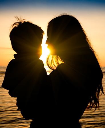 Photo for Mother and son in a deep moment of love during sunset at beach - Concept of union and tender connection between a young mama and his lovely child - Modified shape of silhouettes with filter sun flare - Royalty Free Image