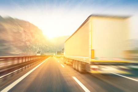 Photo pour Generic semi trucks speeding on the highway at sunset - Transport industry concept with semitruck containers driving to the mountain pass - Warm editing with pop filtered sunshine and blurred edges - image libre de droit