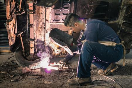 Foto de Young man mechanic worker repairing old vintage car body in messy garage  - Imagen libre de derechos