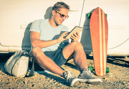 Foto de Young hipster man with tablet sitting next his car - Concept of modern technologies mixed with a vintage lifestyle - Retro filtered look - Imagen libre de derechos