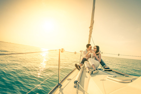 Foto de Young couple in love on sail boat with champagne at sunset - Happy exclusive alternative lifestye concept  - Soft focus due to backlight on vintage nostalgic filter - Fisheye lens and tilted horizon - Imagen libre de derechos
