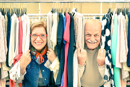 Foto de Playful senior couple at weakly flea market - Concept of active elderly with mature man and woman having fun and shopping in the old town - Happy retirement moments on a warm vintage nostalgic look - Imagen libre de derechos