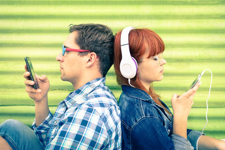 Foto de Hipster couple in disinterest moment with mobile phones - Concept of apathy sadness and isolation using new technologies - Boyfriend and girlfriend with smartphones addiction - Vintage filtered look - Imagen libre de derechos
