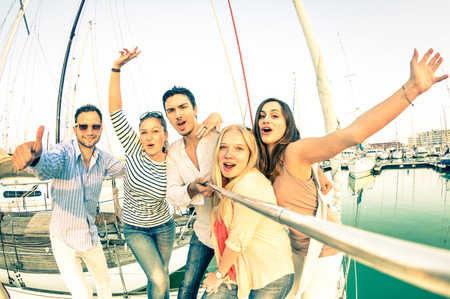 Photo pour Best friends using selfie stick taking pic on exclusive luxury sailing boat - Concept of friendship and travel with young people and new technology  trends - Bright nostalgic desaturated color tones - image libre de droit