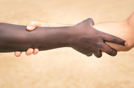 Photo pour Black and white hands in modern handshake to show each other friendship and respect - Helping and respecting each other against racism - Slightly crispy detailed filtered look on defocused background - image libre de droit