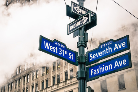 Foto de Modern street sign and vapor steam in New York City - Urban concept and road traffic directions in Manhattan downtown - American world famous capital destination on dramatic desaturated filtered look - Imagen libre de derechos