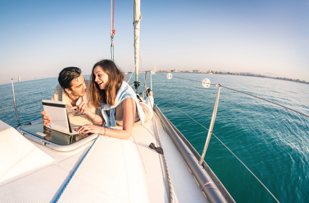 Foto de Young couple in love on sail boat having fun with tablet - Happy luxury lifestyle on yacht sailboat - Technology interaction with satellite wifi connection - Round horizon from fisheye lens distortion - Imagen libre de derechos