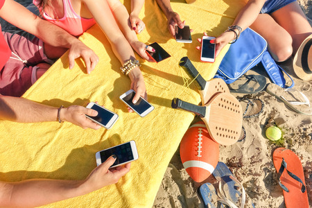 Foto de Group of multiracial friends having fun together with smartphone - Closeup of mixed hands social networking with mobile smart phone in sunny day - Technology concept in summer beach everyday lifestyle - Imagen libre de derechos