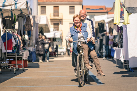 Foto de Happy senior couple having fun with bicycle at flea market - Concept of active playful elderly with bike during retirement - Everyday joy lifestyle without age limitation in a spring sunny afternoon - Imagen libre de derechos