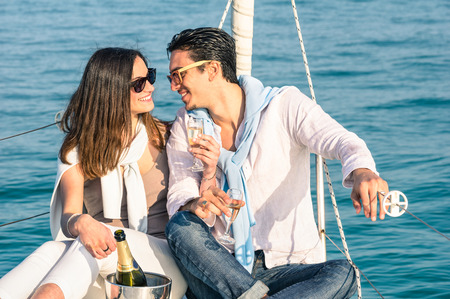 Photo pour Young couple in love on sail boat with champagne flute glasses  Happy exclusive alternative lifestye concept  Boyfriend and girlfriend flirting on luxury sailboat  Sunny afternoon color tones - image libre de droit