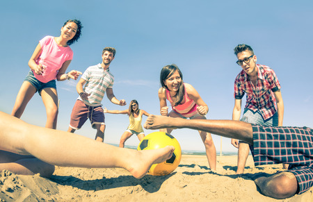 Group of multiracial friends playing beach soccer at beginning of summer  Concept of multi cultural friendship fun and sport against racism  Vintage filter with main focus on girl near the ball