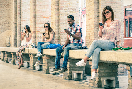 Foto de Group of young multiracial friends using smartphone with mutual disinterest towards each other  Technology addiction in actual lifestyle  Soft vintage filtered look with main focus on male person - Imagen libre de derechos